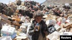 Un enfant boit un jus périmé sur une décharge à Sanaa, au Yémen.