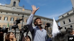 "Five-Star Movement Lawmaker Alessandro Di Battista uses a megaphone to talk with demonstrators of the Liberation of Italy Movement as they stage a protest outside the Italian Parliament against the government-proposed electoral law ""Rosatellum"" in Rome, Oct. 10, 2017."
