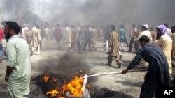 ພວກປະທ້ວງໃນປາກິສຖານ ພາກັນຈູດຢາງລົດ ຢູ່ທາງຫຼວງສາຍນຶ່ງ ໃນນະຄອນ Rawalpindi (21 ກັນຍາ 2012)