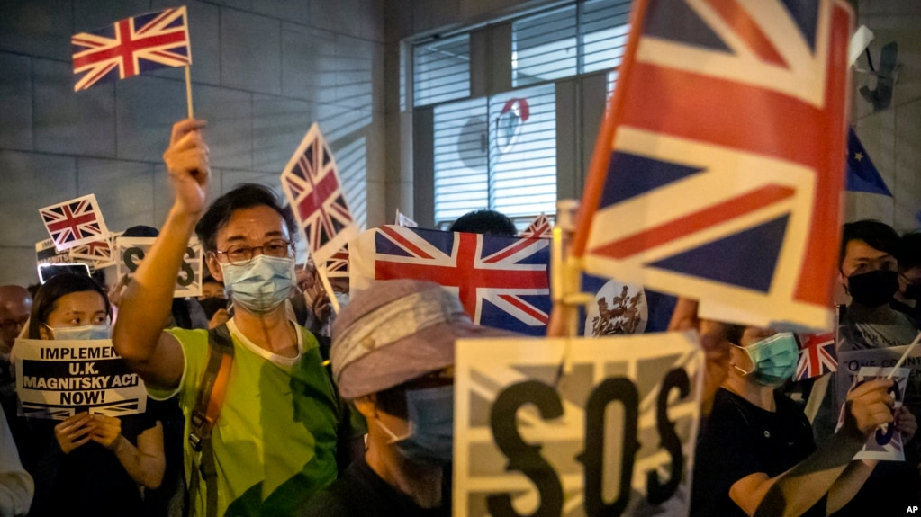 In this Oct. 23, 2019, file photo, demonstrators wave British flags during a rally outside the British Consulate in Hong Kong. (AP Photo/Mark Schiefelbein, File)