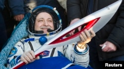 Russian cosmonaut Fyodor Yurchikhin holds the torch of the 2014 Sochi Winter Olympic Games after landing near the town of Zhezkazgan in central Kazakhstan, Nov. 11, 2013.