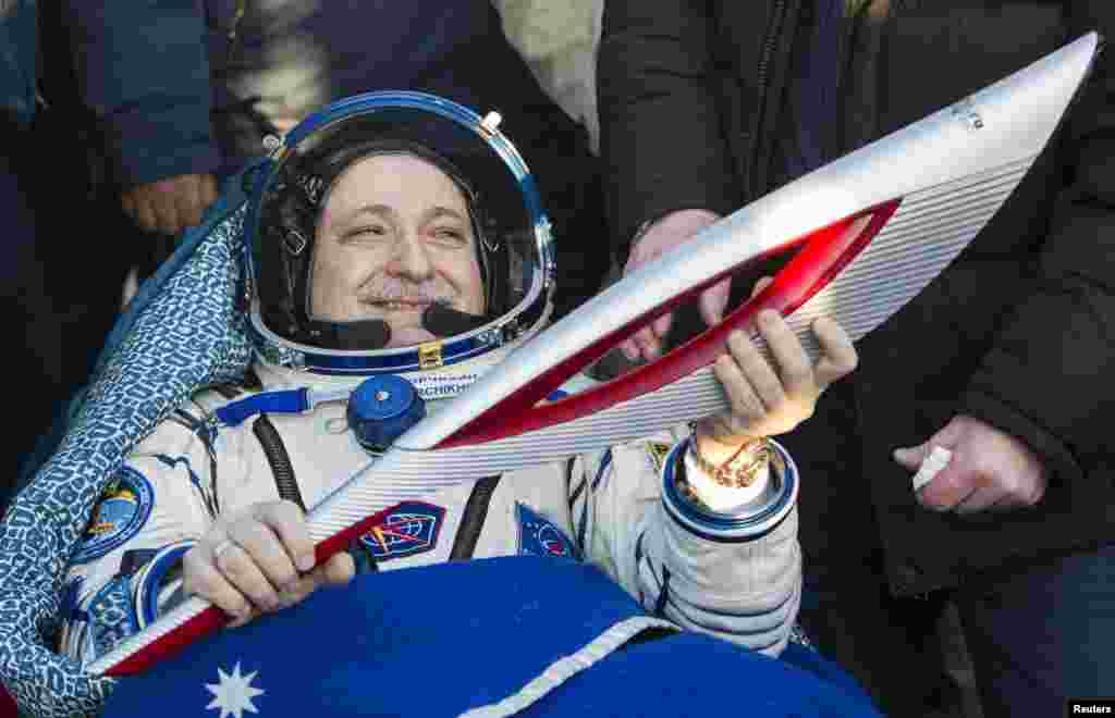 Russian cosmonaut Fyodor Yurchikhin holds the torch of the 2014 Sochi Winter Olympic Games after landing near the town of Zhezkazgan in central Kazakhstan.