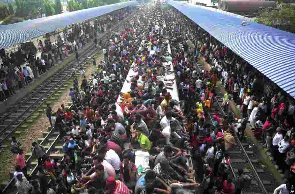 Muslims travel on the roof of a train as they head to their homes ahead of Eid al-Adha as others wait at a railway station in Dhaka, Bangladesh, Oct. 15, 2013.
