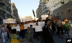 FILE - Activists in Syria's besieged Aleppo protest against the United Nations for what they say is its failure to lift the siege of their rebel-held area, Sept. 13, 2016.