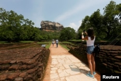 A tourist take pictures of the UNESCO listed World Heritage Site Sigiriya Rock Fortress in Sigiriya, Sri Lanka October 11, 2018. REUTERS/Dinuka Liyanawatte