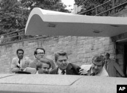 U.S. President Ronald Reagan waves and then looks up before being shoved into the President's limousine by secret service agents after being shot outside a Washington hotel Monday, March 30, 1981. (AP Photo/Ron Edmonds)