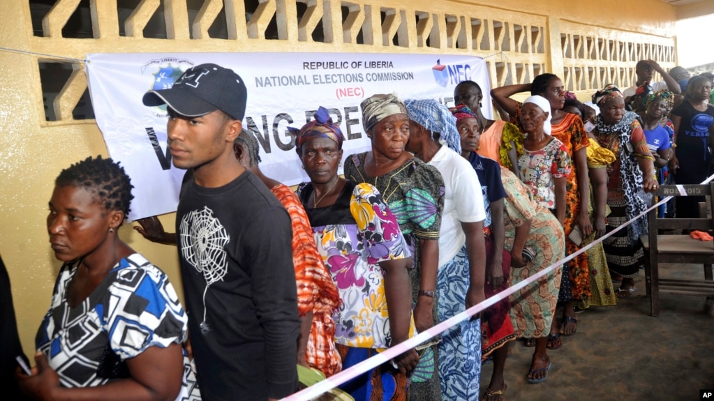 People wait to cast their votes during a Presidential election in Monrovia, Liberia, Oct. 10, 2017. Liberians head to the polls, Dec. 25, 2017, for a runoff election between a former international soccer star and the vice president to replace Africa's first female head of state.