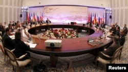 Participants sit at a table during talks on Iran's nuclear program in Almaty, February 26, 2013.