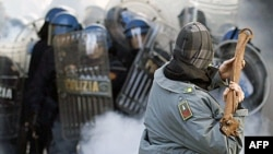 Một người biểu tình ném một thanh kim loại vào cảnh sát trong cuộc biểu tình chống chính phủ tại Rome, 14/12/2010