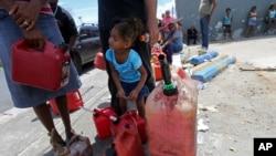 在波多黎各的圣胡安市,一个3岁小孩和家人一起在加油站外面排队(2017年9月25日)