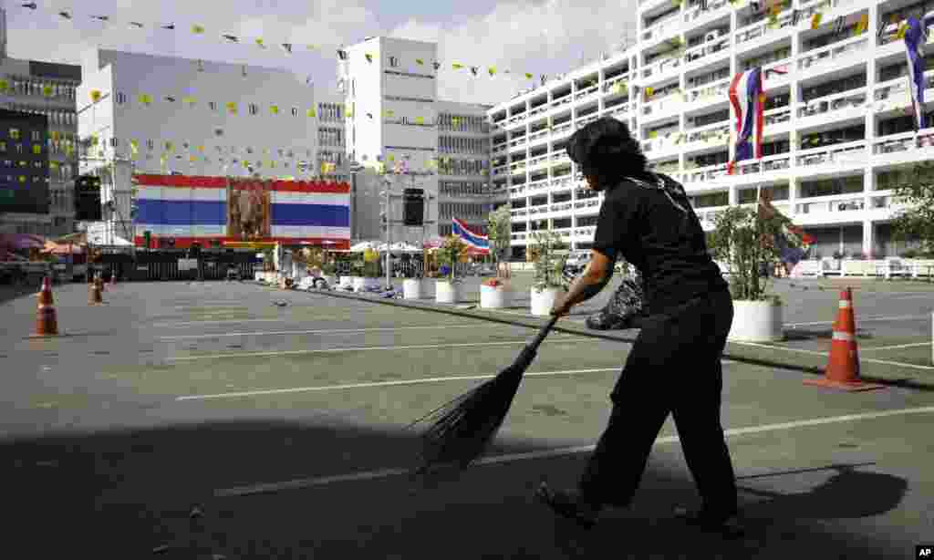 An anti-government protester cleans the ground near an empty parking lot of the Finance Ministry in Bangkok, Dec. 6, 2013.
