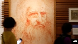 Visitors look at a portrait drawing of Italian Renaissance painter, scientist and inventor Leonardo Da Vinci during a permanent exhibition on Da Vinci, on the exact day commemorating the 500th anniversary of his death, in Rome, Thursday, May 2, 2019.