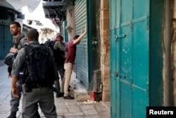 Israeli border policemen search a Palestinian man in Jerusalem's Old City, July 14, 2017.
