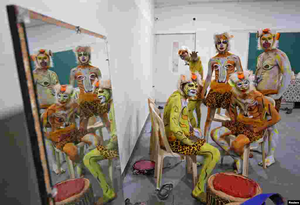 Artists painted to look like tigers are reflected in a mirror backstage as they wait to perform during a cultural event in Bengaluru, India.
