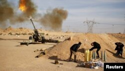 FILE - Libya Dawn fighters fire an artillery cannon at Islamic State militants near Sirte.