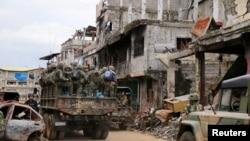 Truk militer yang penuh dengan tentara pemerintah melewati rumah-rumah dan gedung-gedung yang rusak seiring dengan berlanjutnya penyerangan terhadap militan pendukung ISIS. yang merebut distrik Mapandi di Kota Marawi, Filipina, 13 September 2017.