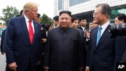 2019年6月30日特朗普(左)在韩国非军事区板门店边境村与朝鲜领导人金正恩(中)和韩国总统文在寅(右)会面。