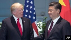 FILE - U.S. President Donald Trump and Chinese President Xi Jinping arrive for a meeting on the sidelines of the G-20 Summit in Hamburg, Germany.