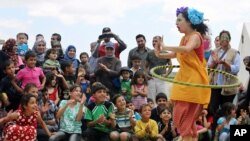 """Badut Lebanon Sabine Choucair, anggota """"Clowns Without Borders,"""" tampil menghibur anak-anak di kamp pengungsi Suriah di Chtoura, di lembah Bekaa, Lebanon. (AP/Bilal Hussein)"""