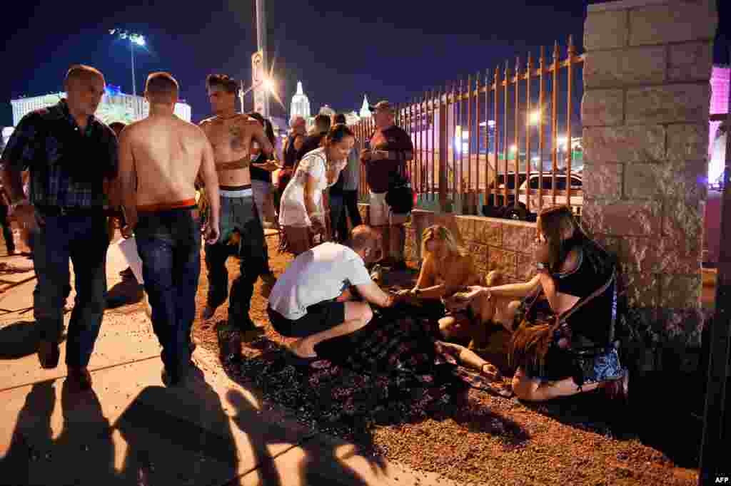 People tend to the wounded outside the Route 91 Harvest Country music festival grounds after an apparent shooting on Oct. 1, 2017 in Las Vegas, Nevada.