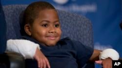نئے ہاتھ حاصل کرنے والا بچہ زائن ہاروی پریس کانفرنس کے دوران مسکرا رہا ہے۔