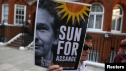 A supporter of WikiLeaks founder Julian Assange holds a placard during a gathering outside the Ecuadorian Embassy in London, June 19, 2015.