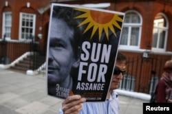 Seorang pendukung pendiri WikiLeaks Julian Assange memegang sebuah placard dalam sebuah pertemuan di luar kedutaan Ekuador di London, 19 Juni 2015.