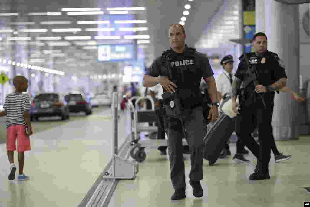 A Miami-Dade police officer, left, and a U.S. Customs and Border Protection officer, right, patrol outside of the departures area at Miami International Airport in Miami, Florida. There is increased security at the airport on this Independence Day holiday weekend after Tuesday's terrorist attacks at Istanbul's Ataturk International Airport.