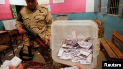 An Egyptian army soldier stands guard as officials count ballots after polls closed during the final stage of a referendum on Egypt's new constitution at the constitutional referendum commission in Cairo, Egypt, Jan. 15, 2014.