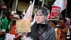 នៅខាងក្រៅស្ថានទូតមីយ៉ាន់ម៉ា ក្នុងរដ្ឋធានីហ្សការតា ស្រ្តីម៉ូស្លីមពាក់មុខរូបរដ្ឋមន្រ្តីការបរទេសមីយ៉ាន់ម៉ា Aung San Suu Kyi ក្នុងពេលប្រមូលផ្តុំប្រឆាំងតវ៉ាការកាប់សម្លាប់ជនជាតិភាគតិច រ៉ូហ៊ីងយ៉ា (រូបភាពថ្ងៃទី២៥ ខែវិច្ឆិកា ឆ្នាំ២០១៦)។