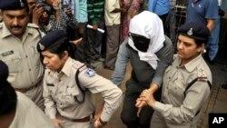 Seorang perempuan Swiss (tengah) berdasarkan keterangan dari polisi, telah diperkosa oleh sekelompok laki-laki saat bersepeda dengan suaminya dikawal polisi India untuk menjalani pemeriksaan medis di rumah sakit Gwalior, India (16/3).