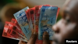 FILE - Ghana labor unions want the government to act to halt depreciation of Ghana's currency, the cedi.