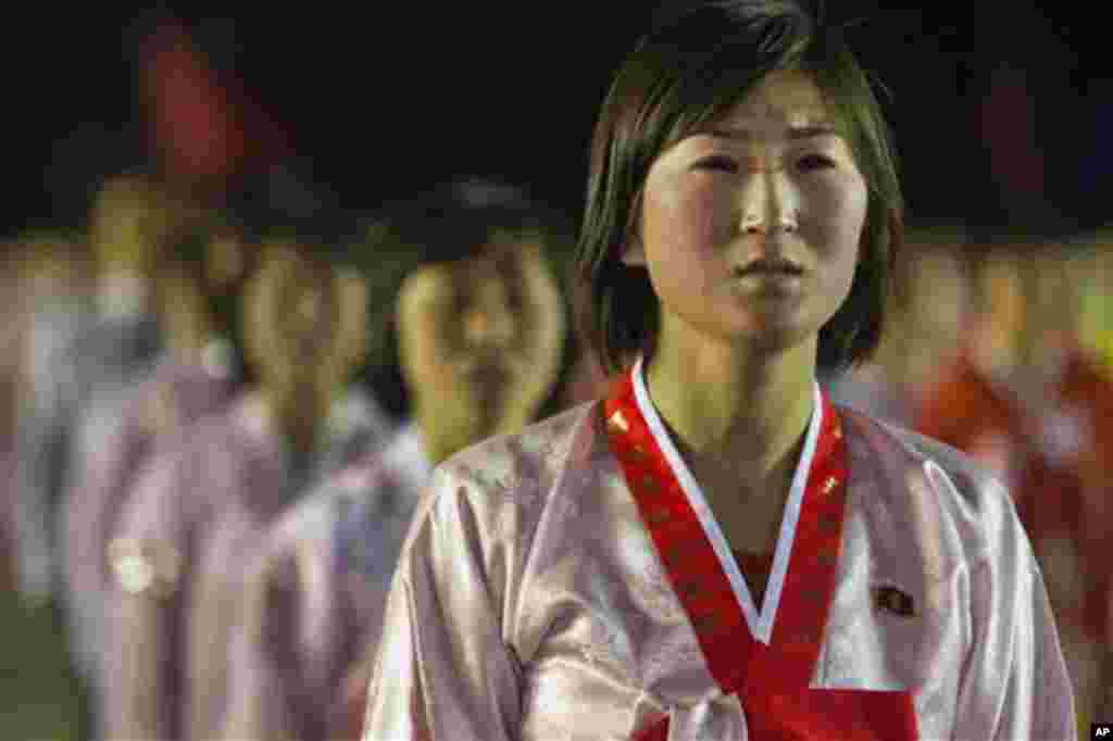 A North Korean woman weeps and sings a song about North Korean leader Kim Jong Un at the end of a mass dance performance in Kim Il Sung Square in Pyongyang, North Korea, Monday April 16, 2012. (AP Photo/David Guttenfelder)