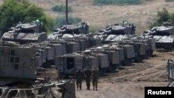 시리아 골란고원에서 이스라엘 군인들이 무장 장갑차 사이로 걸어가고 있다.
