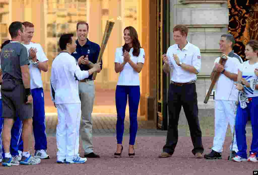 這張由倫敦奧組委提供的照片顯示第170號火炬手在白金漢宮把奧運火炬交給第171號火炬手。觀看交接的包括劍橋公爵和公爵夫人以及哈里王子(7月26日)。