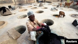 FILE - A man dyes fabrics in traditional styles in Kano, Nigeria.