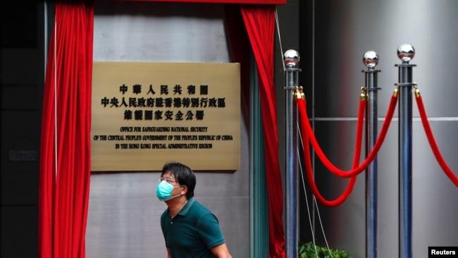 一名男子走过香港一家酒店外北京新设的驻港国安公署的牌子。(2020年7月8日)