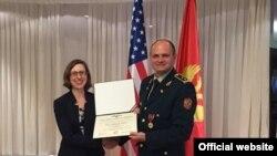 Načelnik Direkcije za međunarodnu saradnju u Ministarstvu odbrane Crne Gore Velibor Bakrač sa odlikovanjem koje mu je uručila vršilac dužnosti zamjenika pomoćnika sekretara za odbranu SAD Lora Kuper (gov.me)