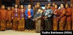 Dalang Purbo Asmoro sambil memegang wayang Biden dan Harris (tengah) beserta kru karawitan melakukan foto bersama pegiat seni budaya asal Amerika Serikat, Kitsie Emerson (tengah- baju merah biru), Sabtu, 30 Januari 2021. (Foto : VOA/ Yudha Satriawan)