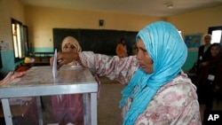 A woman casts her ballot at a polling station in Rabat, November 25, 2011.