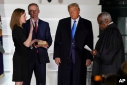 President Donald Trump watches as Supreme Court Justice Clarence Thomas administers the Constitutional Oath to Amy Coney Barrett on the South Lawn of the White House White House in Washington, Monday, Oct. 26, 2020.