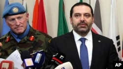 Lebanese Prime Minister Saad Hariri, right, speaks to journalists, as he stands next of Head of Mission and Force Commander of UNIFIL, Maj. Gen. Michael Beary, left, at U.N. peacekeepers headquarters, at the coastal border town of Naqoura, south Lebanon, April 21, 2017.