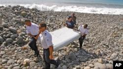 法国警方人员手持或许是马航370航班飞机上掉下来的残骸