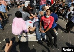Protesters, who support ousted Egyptian President Mohamed Morsi, transport injured people during clashes at Ramses Square in Cairo, Aug. 16, 2013