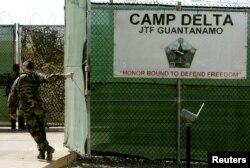 25 Ağustos 2005 yılına ait bu fotoğrafta bir ABD askeri, Küba'nın Guantanamo Koyu'ndaki askeri üste bulunan hapishanenin giriş kapısını kapatırken görüntülenmiş.