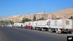 ຂະບວນລົດ ຊ່ອຍເຫຼືອດ້ານມະນຸດສະທຳ ລໍຖ້າຢູ່ດ້ານໜ້າ ຫ້ອງການ ອົງການບັນເທົາທຸກ ແລະການທຳງານ ຂອງອົງ ການສະຫະປະຊາຊາດ (UNRWA) ກ່ອນທອອກເດີນທາງ ເຂົ້າໄປໃນ ເມືອງ Madaya, al-Zabadani ແລະ al-Moadhamiya ທີ່ເປັນເຂດປົກຄອງ ຂອງພວກຕໍ່ຕ້ານ ລັດຖະບານ ທີ່ຖືກປິດລ້ອມ ໂດຍລັດຖະບານ ຊີເຣຍ.