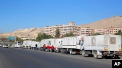 FILE - A convoy of humanitarian aid trucks waits before making its way into government-besieged towns in the Damascus countryside as part of a U.N.-sponsored aid operation, in Damascus, Syria, Feb. 17, 2016.