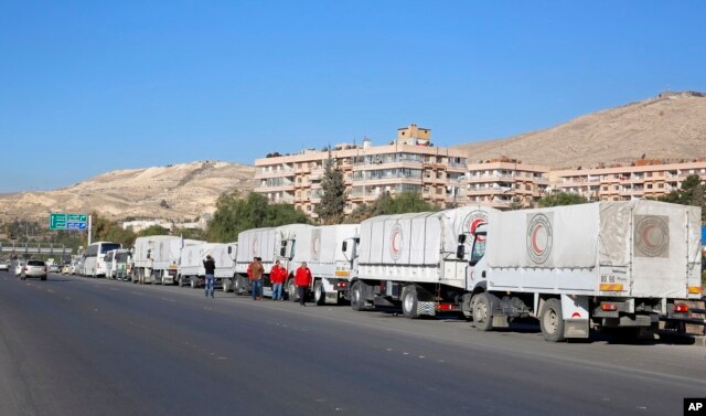 FILE - A convoy of humanitarian aid waits in front of the United Nations Relief and Works Agency (UNRWA) offices before making their way into the government besieged rebel-held towns of Madaya, al-Zabadani and al-Moadhamiya in the Damascus countryside, as