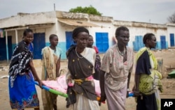 Women carry the body of a civilian killed in the center of Malakal, Upper Nile State in South Sudan, Jan. 21, 2014.