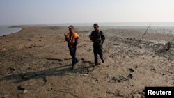 Bangladesh coast guards walk in the Thengar Char island in the Bay of Bengal, Bangladesh, Feb. 2, 2017.